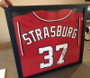 Here we framed a signed jersey of Washington Capitals pitcher Stephen Strasburg, stitching it down to a navy blue backing and fitting it inside a matching navy blue frame under non-glare plexiglass.